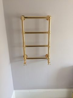 Install of gold plated towel rail in new bathroom